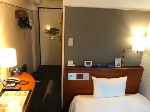 アパホテル金沢駅前のシングルルームの部屋の机とベッドと壁にかかるハンガーと部屋の入口