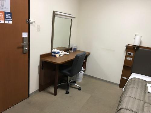 コンフォートホテル富山駅前のシングルルームの部屋の机とベッドの間のスペース