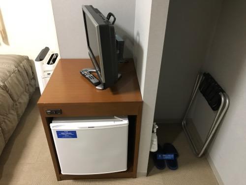 コンフォートホテル富山駅前のシングルルームの空気清浄機、テレビ、冷蔵庫、スリッパ