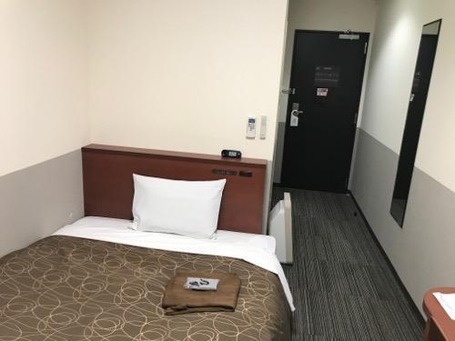 金沢ゆめのゆ(HOTELゆめのゆ)のシングルルームのベッドと入口ドア