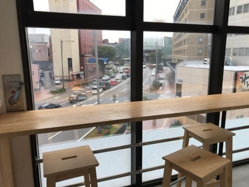 Blue Hour Kanazawaの共用スペースの机と窓から見える風景(朝の様子)