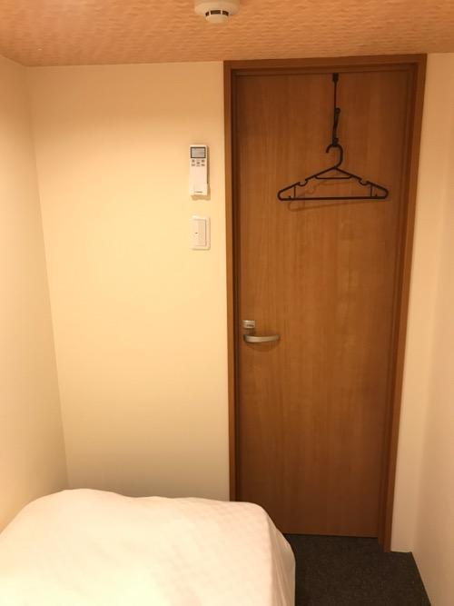 炭の湯ホテルの宿泊用の部屋「コンパクトルーム シングル」の部屋の入口ドアを見た時の様子