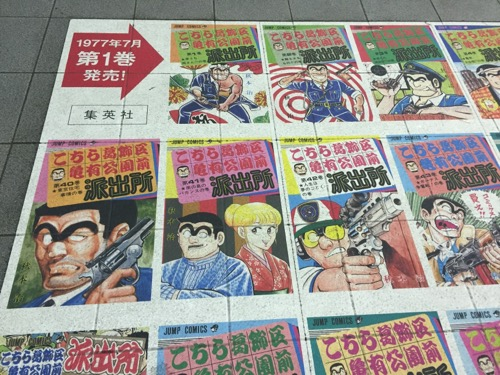 JR亀有駅改札口前の床に貼られたこち亀コミックスの表紙集(第1巻、第2巻など)