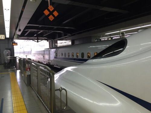 品川駅新幹線ホームに停車しつつある新幹線のぞみ25号博多行の先頭車両・進行方向側