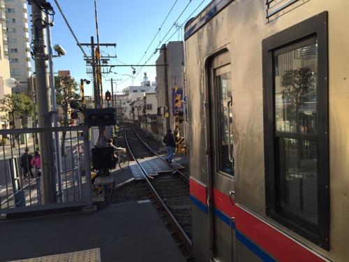 京成金町駅ホームの端から見た目前の踏切と停車中の電車