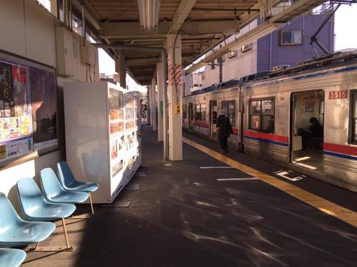 京成金町駅ホームの青い椅子、自動販売機、停車中の電車