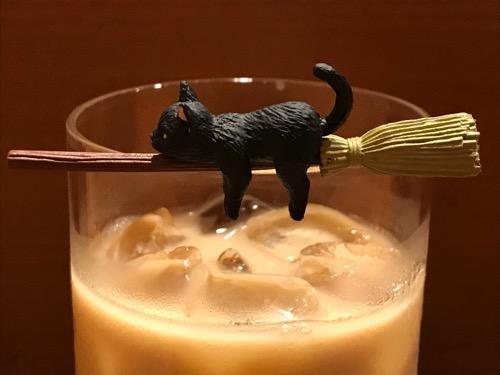 カフェベローチェ綾瀬店のアイスカフェオーレのコップのフチにホウキでまたがる猫(側面・拡大)
