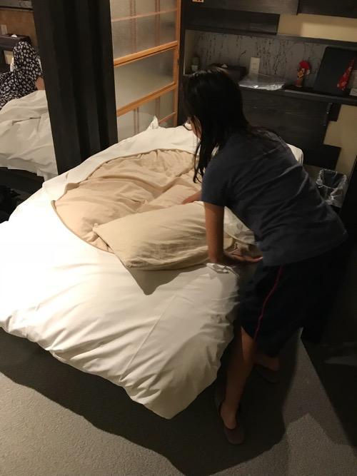 湯之谷温泉のゲストハウス部屋「海」の部屋内のベッド(シーツ等を装着する娘)