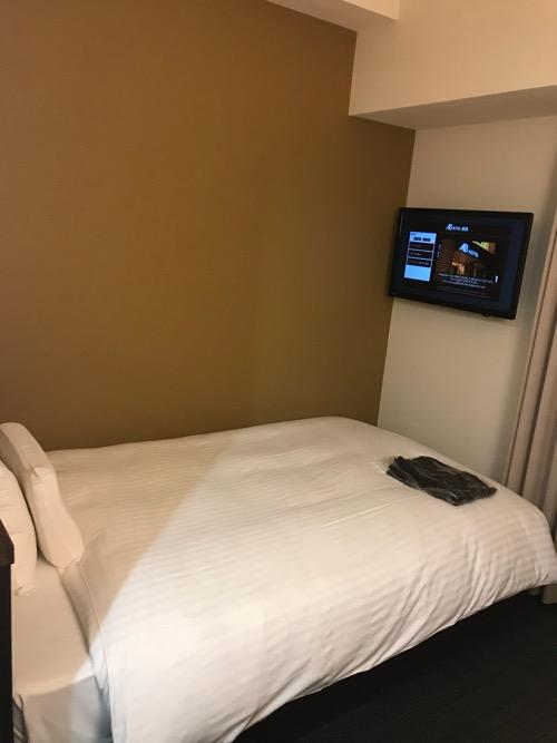ABホテル豊橋のセミダブルベッドと壁掛けテレビ