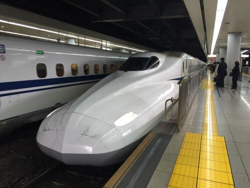 品川駅新幹線ホームに停車しつつある新幹線のぞみ25号博多行