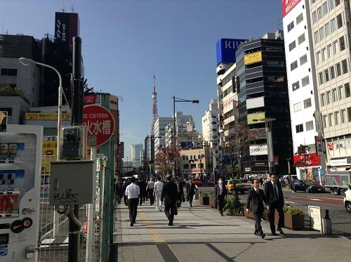 都営地下鉄・大門駅(浜松町)の入口付近を行き交う人々と、遠くに見える東京タワー
