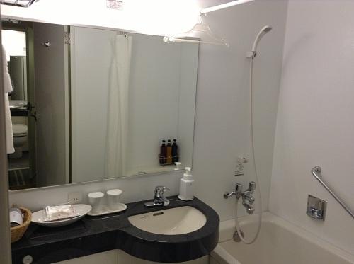 ホテルサンルート有明室内の洗面台と鏡とシャワーとハンガー