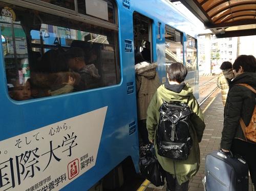 「1 正覚寺下」(1504)という車体の市内電車の乗り口と乗車する客