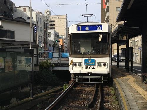 正覚寺下電停から去りゆく市内電車「1 赤迫 AKASAKO」(1504)