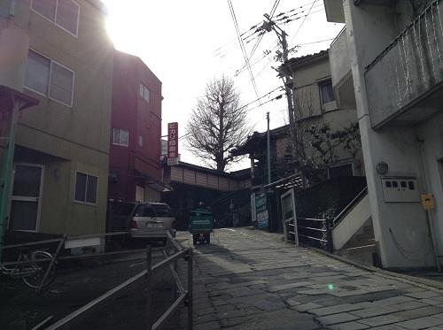 正覚寺電停前の道路から見える石畳の坂道と正覚寺の門