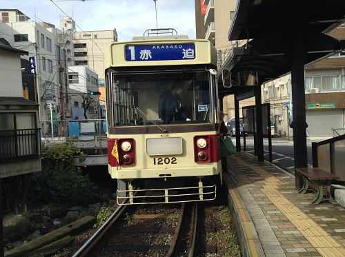 正覚寺下電停に停車中の「1 赤迫 AKASAKO」(1202)という車体の市内電車