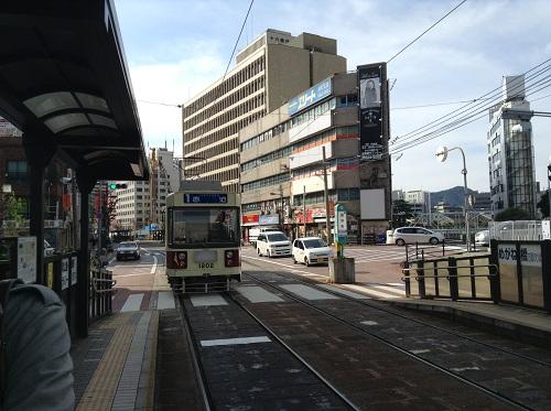 西浜町電停ホームより去りゆく市内電車「1 赤迫 AKASAKO」(1202)」