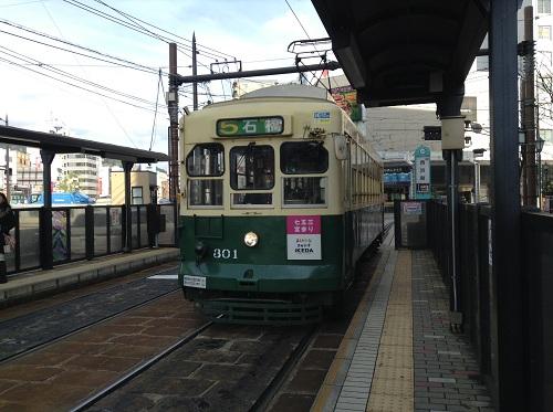西浜町電停ホームに到着しつつある市内電車「5 石橋」(301)