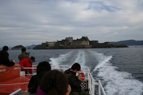 マーキュリー(軍艦島上陸・周遊ツアー船)の船上から去りゆく軍艦島を眺める人々