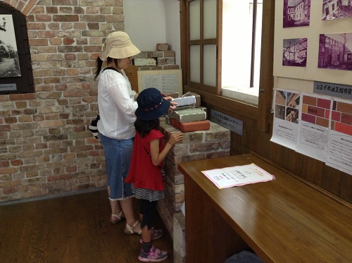 おおず赤煉瓦館(愛媛県大洲市大洲60番地)の資料室内で煉瓦積み体験をする妻と娘