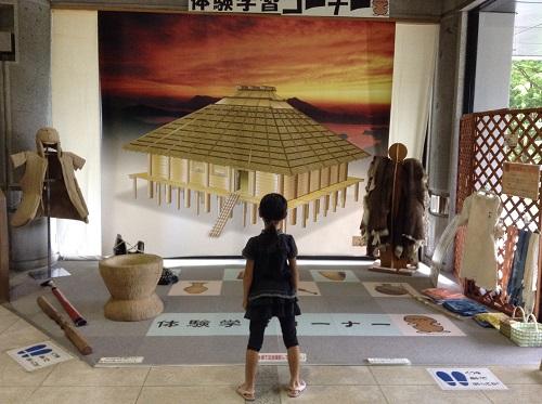 松山市考古館(愛媛県松山市南斎院町乙67番地6)内にある体験学習コーナーとその前に立つ小学3年生の娘