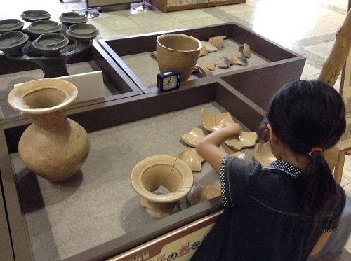 松山市考古館(愛媛県松山市南斎院町乙67番地6)内の土器パズルで遊ぶ小学3年生の娘