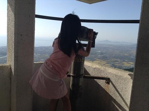 えひめ森林公園 谷上山第2展望台に設置されている双眼鏡(COVAC B345)で伊予市街を眺める娘