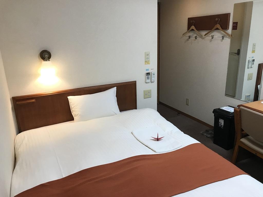 2020年2月 コモドホテル大分 禁煙シングルルーム 足元側から見たベッド、枕、壁のハンガー