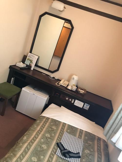 ホテルターミナルインの禁煙シングルAのベッド、机、椅子、冷蔵庫、鏡