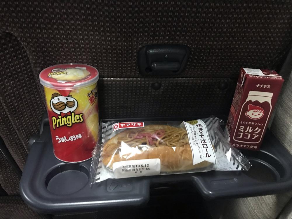 飯田駅からバスタ新宿行の高速バスの座席のテーブルに並ぶプリングルス、焼きそばロール、チチヤスミルクココア