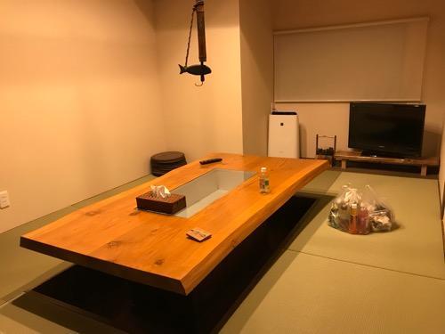 湯之谷温泉の談話室の掘りごたつ式のテーブル、畳、テレビ