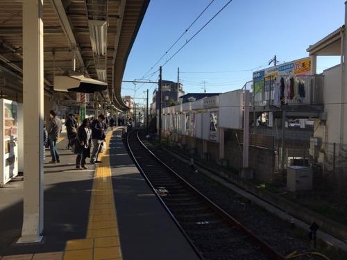 京成金町駅のホームで電車を待つ人々