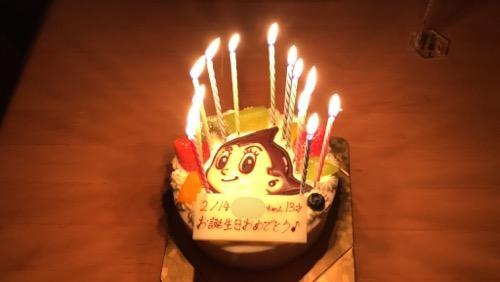 火のついた13本のローソクが立つ鉄腕アトムの誕生日ケーキ