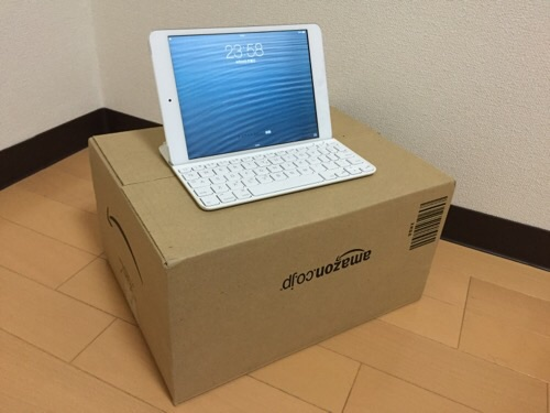 Amazonのダンボール箱(P15 K 12)の上に乗せたブルートゥースキーボード付きのiPad mini