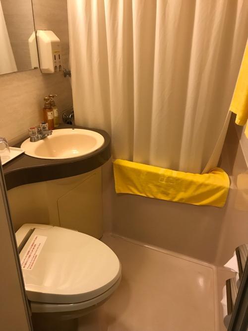 ニイガタステーションホテルのシングルルームのトイレ、洗面台、浴槽、シャワーカーテン