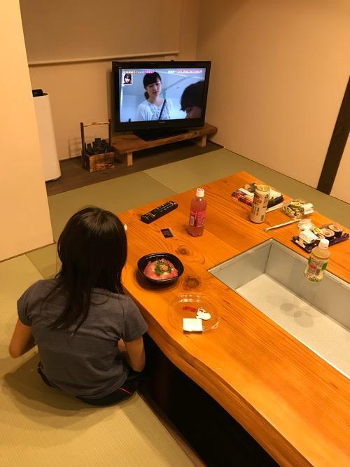 湯之谷温泉の談話室でご飯を食べながらテレビを見る娘