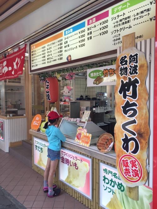 鳴門の渦潮の観光地の売店で阿波名物竹ちくわを買う10歳の娘