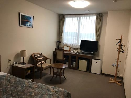 ホテルウェリィスミヨシのシングルルーム室内の様子(机、椅子、窓)
