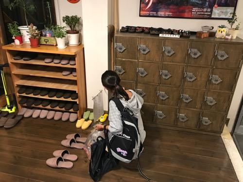 湯之谷温泉の宿泊者専用下駄箱に靴を入れる娘