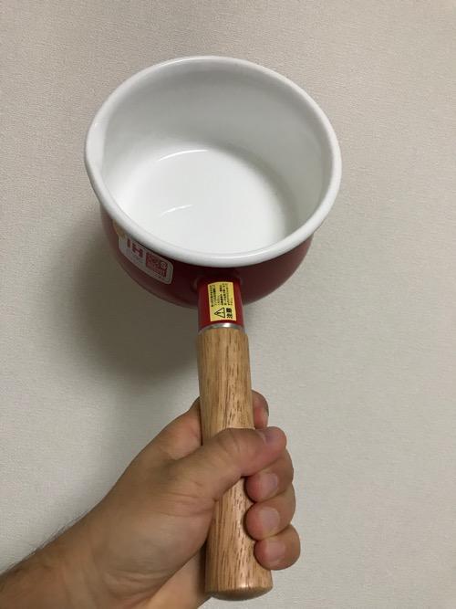 富士ホーロー 蓋付きミルクパン 15cm 1.2L レッドを片手で持った様子