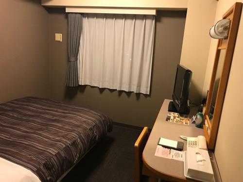ホテルルートイン新潟県庁南の禁煙シングルルームのベッド、机、窓のカーテン