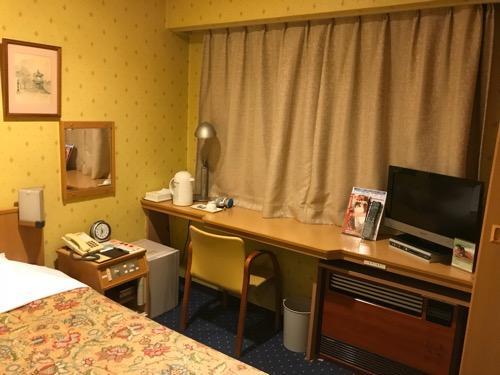 ニイガタステーションホテルのシングルルームのベッド、机、椅子、テレビ