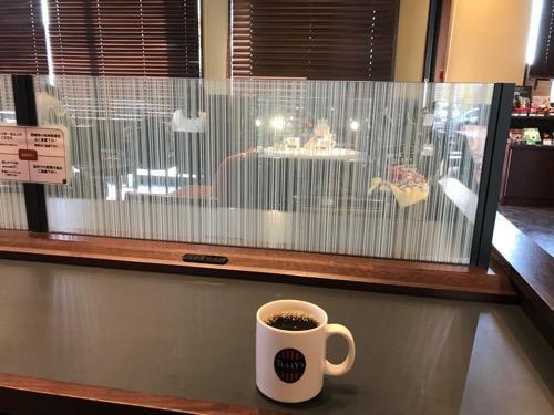 タリーズコーヒー君津駅前店の店内のテーブルにある充電可能なコンセントとトールサイズのマグカップのホットコーヒー