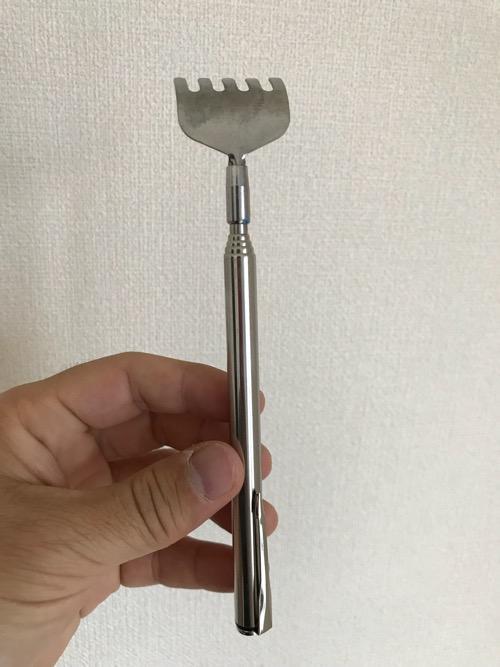 株式会社トレードワン 携帯用スクラッチャー MA・GO・NO・TE(最小化した孫の手を手に持った様子)