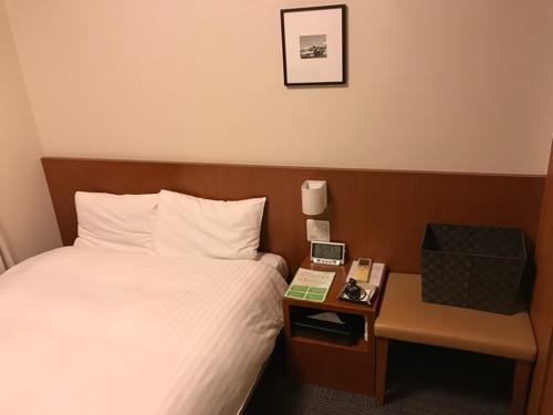 天然温泉 加賀の湧泉 ドーミーイン金沢の禁煙様ダブルルーム室内のシモンズ社製ベッドとパジャマが入っている籠