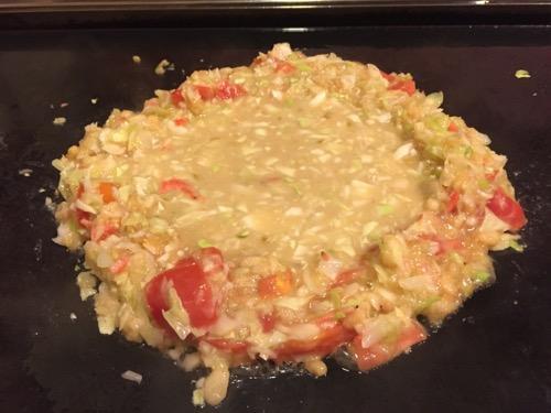 お多福 北千住店のミニトマトチーズもんじゃを鉄板で焼いている途中の様子(土手の中に生地を入れた直後)