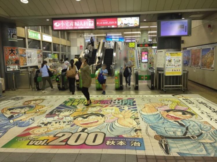 JR亀有駅改札口前の床に貼られたこち亀200巻達成記念のポスター