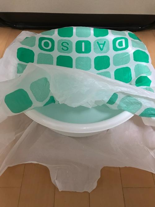 100円ショップ・ダイソーで購入した洗い桶を保温のためにダイソーのレジ袋で覆った様子