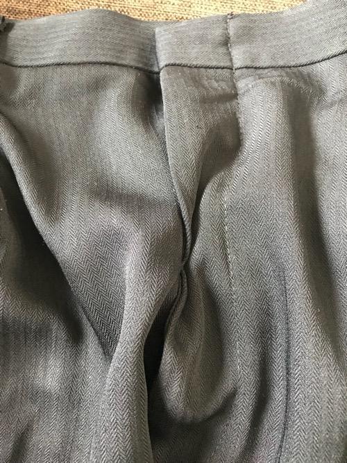 ズボンの壊れたチャックを裏側からダブルクリップで止めて応急処置をした場合に、ズボンを前から見た様子