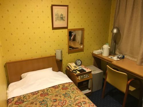 ニイガタステーションホテルのシングルルームのベッド、鏡、ルーム電話、机、椅子
